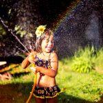 Safe backyard tips | Kid in the garden hose